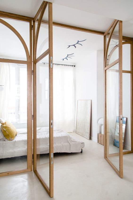 a light-filled neutral bedroom with glass walls, a bed, a mirror and some art is very cool and feels very airy