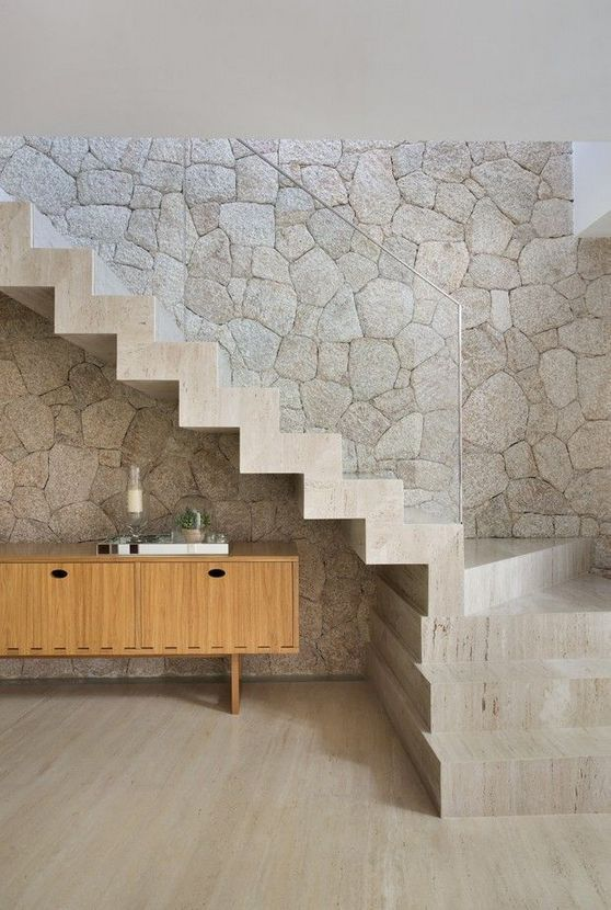 a  limestone statement wall and a matching neutral staircase with clear glass railing for an ultimate contemporary space