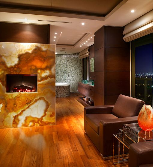 a lit up onyx slab statement wall with a fireplace is pure luxury that takes your breath away