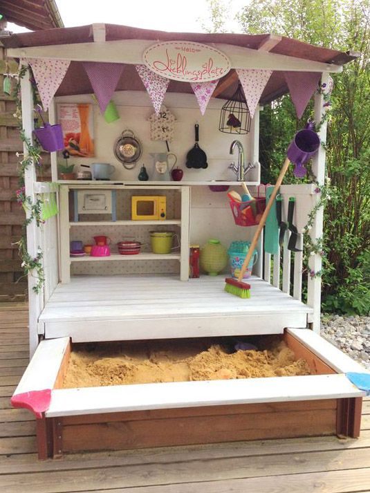 a lovely shed with toy tableware and other stuff, with buntings and greenery plus a sand box is a geat idea