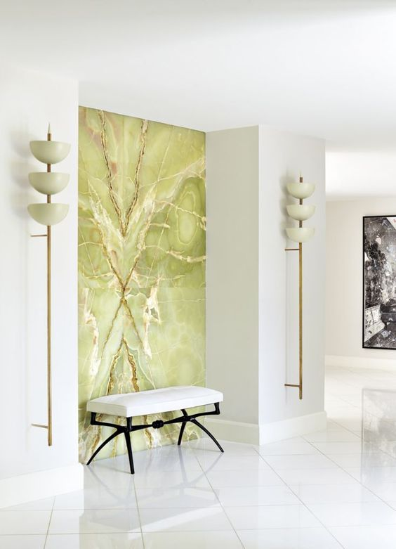 a luxurious white entryway accented with a green onyx statement wall looks really breahttaking