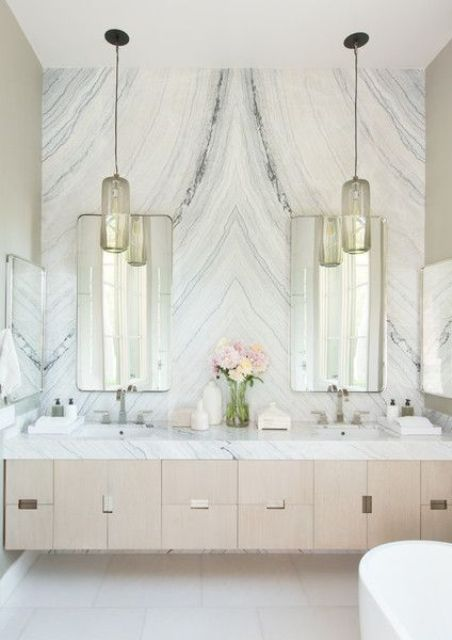 a luxurious white marble accent wall completes the neutral and veyr chic look of this bathroom