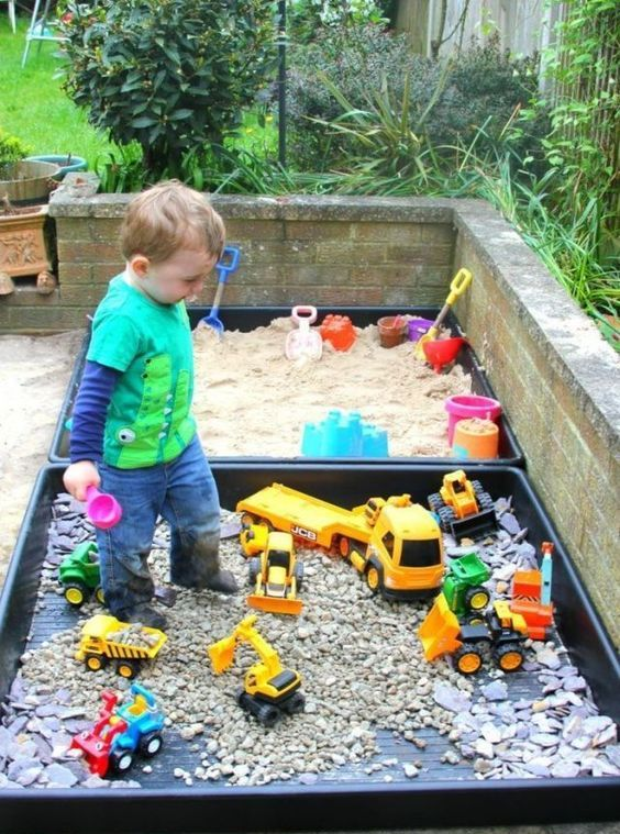 a mini sand box and a mini toy playground with colorful toy cars for a little boy to spend time outdoors