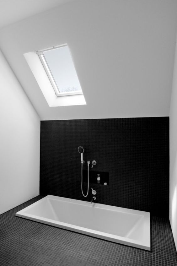 a minimal monochromatic bathroom in black and white, with skylights and a sunken bathtub is a very simple and stylish space