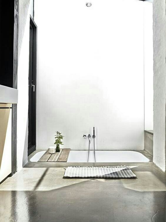 a minimalist bathroom done in concrete and with a white sunken bathtub is very simple, casual and with no fuss