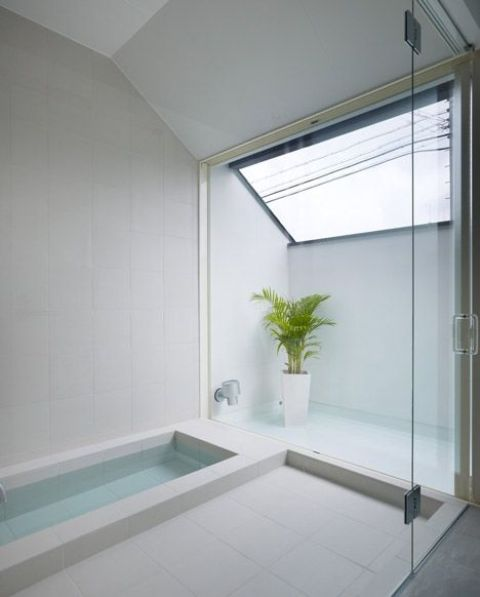 a minimalist bathroom with a skylight, a sunken bathtub, a shower space and a potted plant is clad with neutral tiles