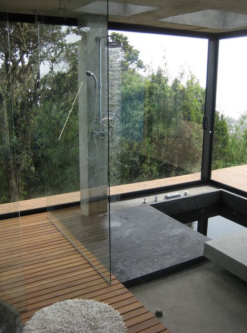 a minimalist bathroom with a wooden deck, a concrete shower space and a sunken bathtub plus a panoramic view
