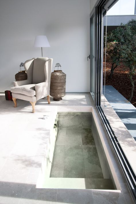 a minimalist sunken bathtub right in the bedroom, with a sliding door to make this space outdoor at once