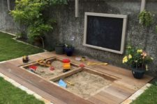 a modern outdoor play space with a sandbox and a deck around it, potted blooms, a chalkboard on the wall
