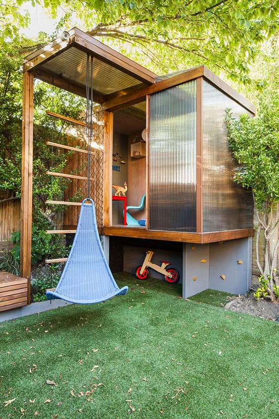 a modern tree house with a climbing wall and lots of toys inside, with glass walls and a large swing in front of it