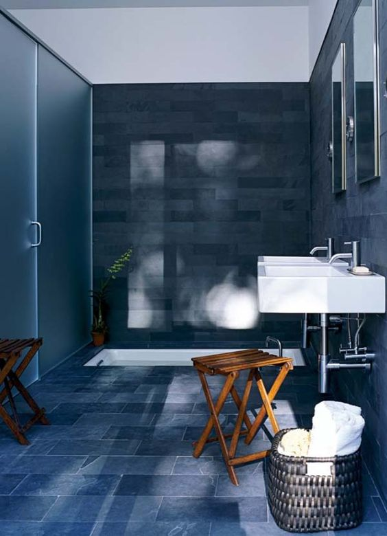 a navy and grey bathroom with a white sunken tub and sinks plus wooden folded stools and a basket for storage