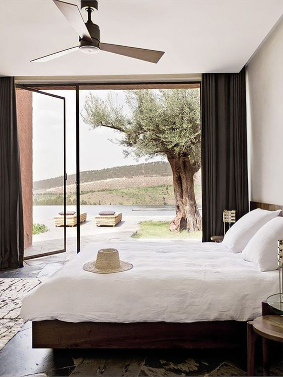 a relaxed modern bedroom with dark wooden furniture, neutral bedding and a glass wall with a door to the terrace plus black curtains