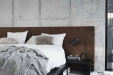 a rough cement accent wall is softened with a brown upholstered headboard and a fluffy rug on the floor