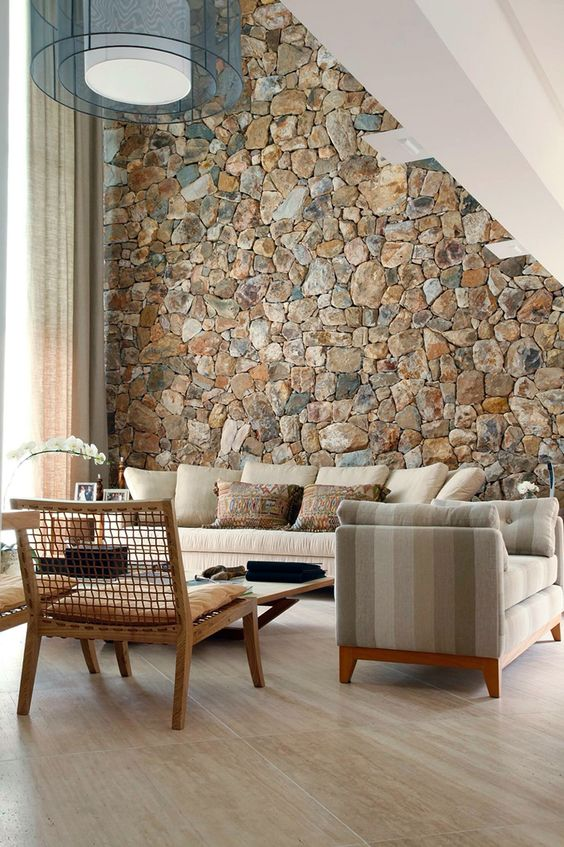a rough stone accent wall adds a natural feel to the contemporary living room and brings a touch of natural color