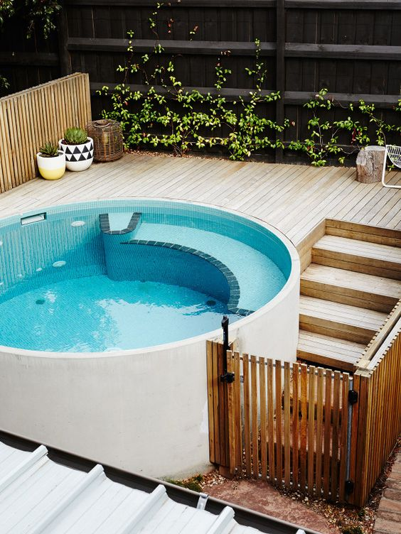 a round plunge pool with a wooden deck and some greenery in pots and on the wall make up a cool small spa