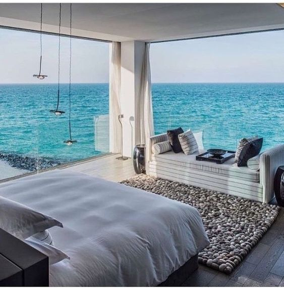 a sea bedroom with glass walls and amazing views, chic white furniture, pendant lamps and a pebble rug is fantastic