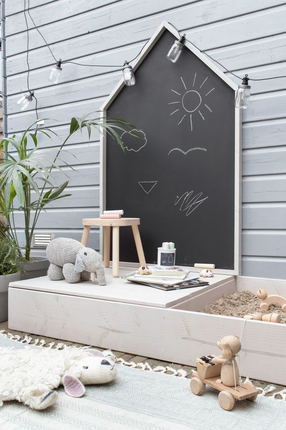 a simple Nordic outdoor play space with a chalkboard, a reading nook, a small sand box and a deck with toys
