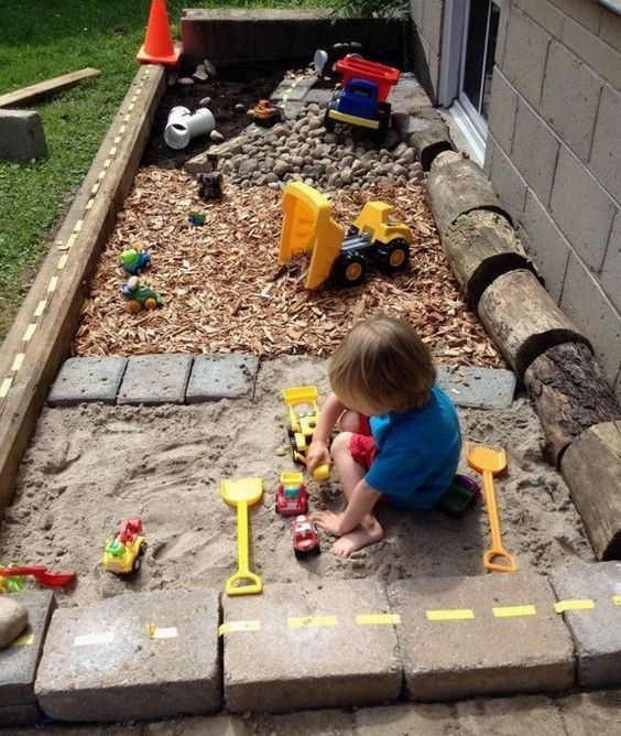 a simple outdoor oasis with a sand box, pebbles and a toy space is built of usual materials that most of have at hand