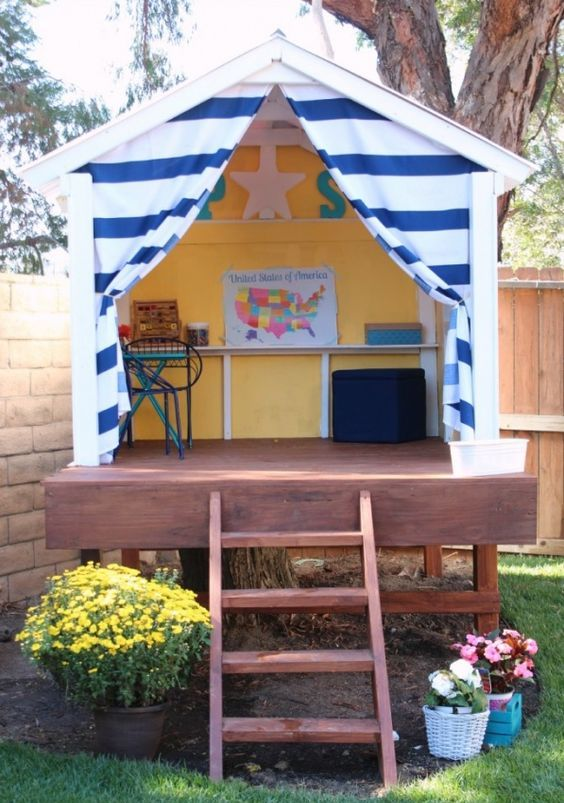 a small backyard house with a creativity space and lots of blooms around will be loved by your kids