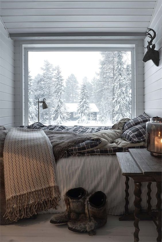 a small chalet bedroom with a glass wall, a bed with plaid bedding, a vintage wooden nightstand and a view of the forest is veyr cozy