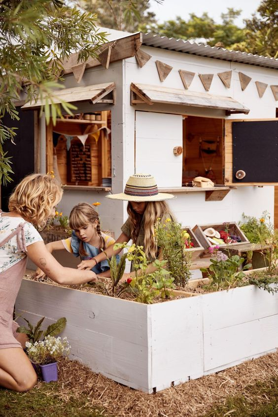 a small garden playhouse with chalkboard shutters, a play garden and a play kitchen for children outdoors