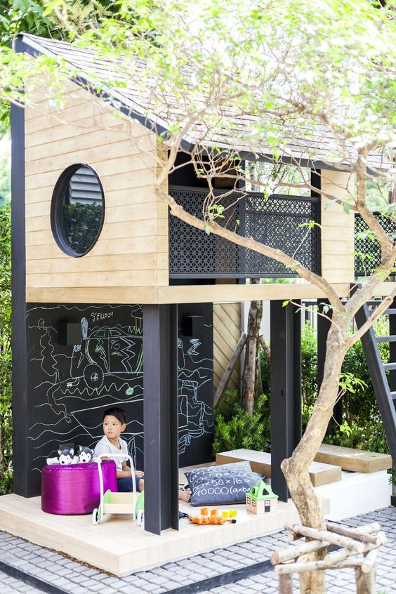 a stylish modern tree house with a ladder and a small yet cozy play space under it, with toys, pillows and other stuff