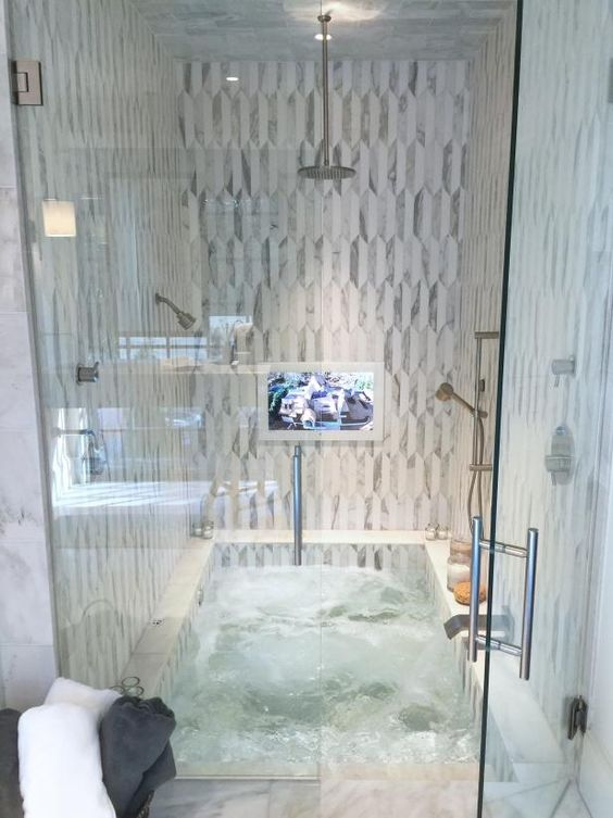 a sunken bathtub combined with a shower space and clad with neutral and catchy tiles is very comfortable and space saving