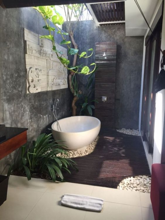 a tiny outdoor space with a wooden deck, pebbles, a shower, a bathtub and greenery growing plus a skylight