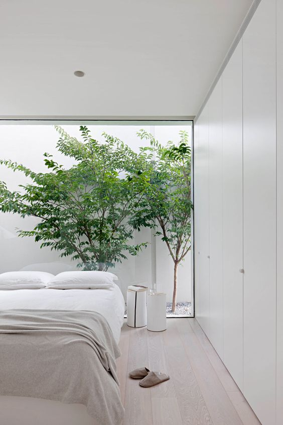 an airy minimalist bedroom in neutrals, with a large bed, white nightstands and a glass wall with a view of the private courtyard