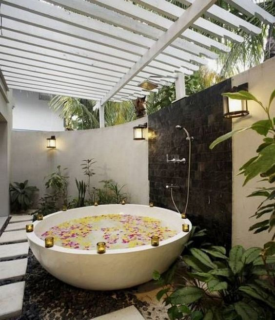 an outdoor bathtub of stone, with candle holders on the edge, with a shower, planted greenery and tall walls for privacy