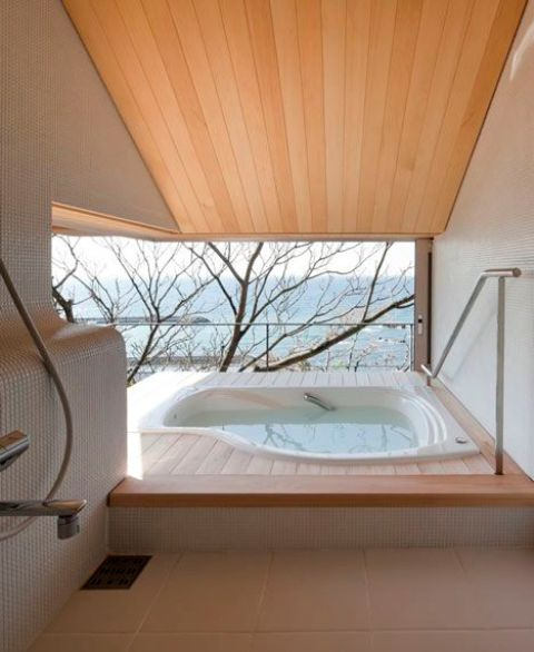 an outdoor indoor minimalist bathroom with an asymmetrical bathtub, a view and a terrace to enjoy the views as much as possible