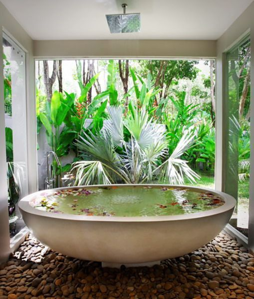 an oval bathtub placed on pebbles feels like a real spa and can be opened up to outdoors any time