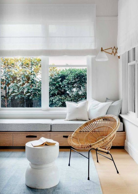 a beautiful contemporary space in light greys, with white Roman shades and a windowsill daybed with pillows, a rattan chair and a side table