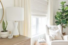 a beautiful creamy space with a neutral Roman shade and creamy curtains to block out the sun when the baby's sleeping