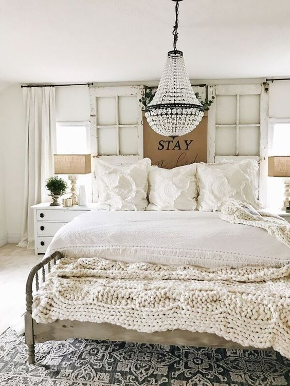 a beautiful shabby chic bedroom with window frames, refined furniture, a crystal chandelier and ruffle bedding