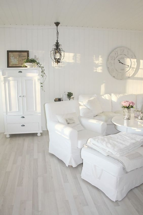 a beautiful white shabby chic living room with stylish vintage furniture, a clock, a chandelier and greenery in pots