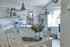 a beautiful white shabby chic space with white cabinets, a white dining set, a crystal chandelier and vintage decor on open shelves