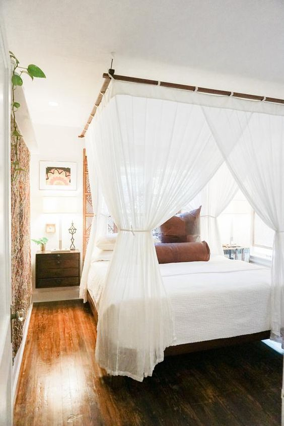 a bed with a bamboo frame and a mosquito net canopy that keeps bugs away and add colonial style to the bedroom