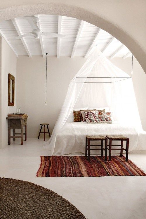 a boho chic bedroom with boho rugs, folksy pillows and a mosquito net canopy over the bed