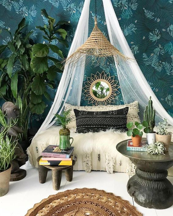a boho desert bedroom with a daybed accented with a mosquito net over it and a wicker lampshade