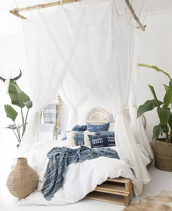 a boho tropical bedroom with mosquito net curtains hanging on bamboo frames looks very welcoming