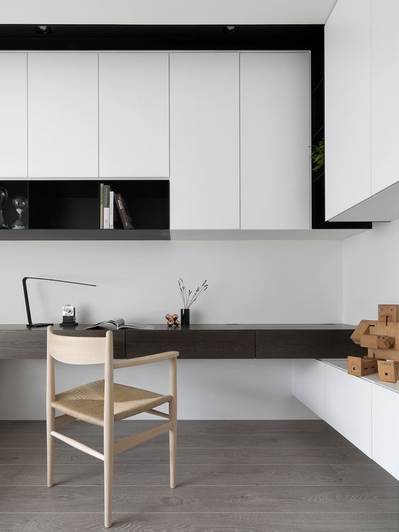 a bold minimalist home office in black and white, with sleek storage units and an open shelf, a built-in dark-stained desk and a woven chair