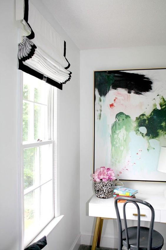 a bright home office nook with a white desk, a grey chair, a bold abstract artwork and a chic black and white Roman shade for a refined touch