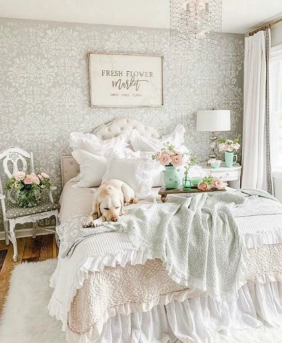 a charming pastel bedroom with sophisticated white furniture, pastel bedding, lots of blooms and a crystal chandelier