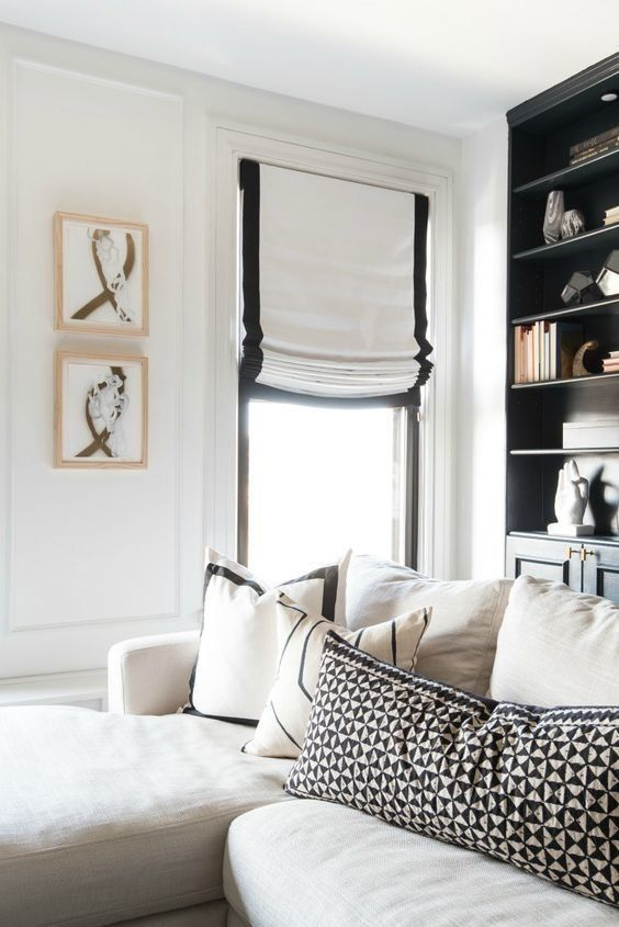 a chic black and white Roman shade adds elegance to the interior and makes it more contrasting and bold blocking out the sun when needed