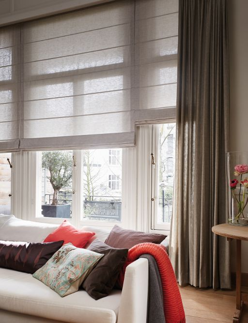a chic contemporary living room with tan Roman shades and brown curtains that provide light blocking and privacy when needed