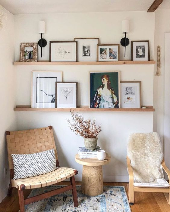 a chic reading nook with a couple of stylish chairs, wodoen ledges for displaying art and photos, a wooden table and a printed rug