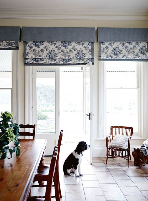 a classic dining room with windows and doors styled with blue floral print Roman shades is a cool bold space