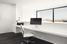 a clean minimalist home office in white, with a dark floor, a window with a view, a floating windowsill desk and a cool white chair