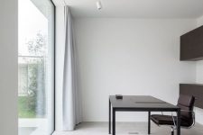 a clean minimalist home office with black storage units, a sleek black desk and a chair, a glazed wall for a lovely view